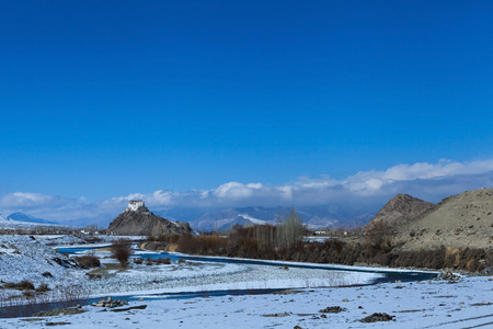 Stakna monastery on the hill with the river bend in foreground during winter in Leh,Ladakh,Kashmir,India