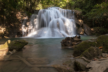 waterfall in tropical forest at the national park in Thailand with tree root under water as foreground Zdjęcie Seryjne