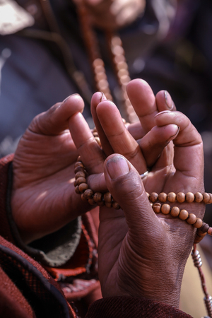 Sacred hand mudra with prayer bead of the male devotee during the Buddhism ceremony at ancient monastery in Leh,Ladakh,Kashmir,India