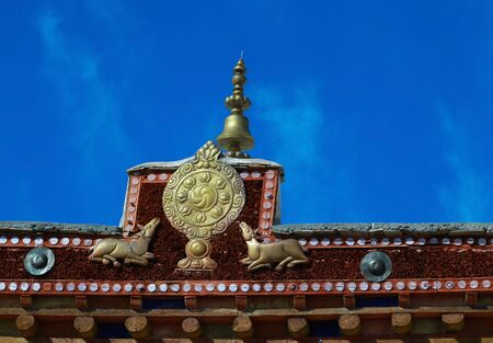 Buddhism symbol,Dharma wheel flanking with deers,on the roof of the ancient monastery,Leh,Ladakh,Kashmir,India