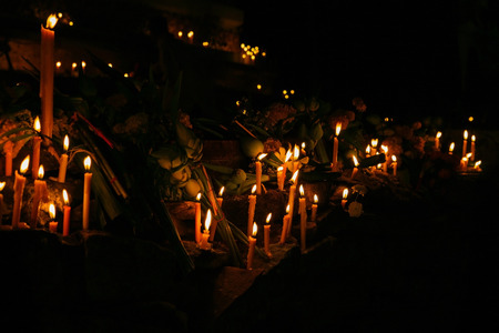 Ritual candles flanking with lotus and other flowers around the sacred pagoda during religious ceremony in an ancient temple at night in Thailand