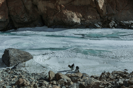 Trekker and porter packing their equipments and gear on frozen river during Chadar(frozen Zanskar river) trek in Leh,Ladakh,Kashmir,India