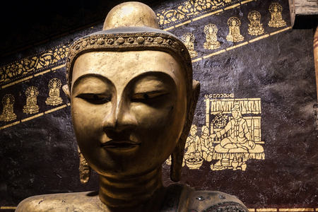 Close up of the golden merciful Buddha head statue.His eyes look down to all mankind with the intention to help them from their sufferings and cycle of birth and death.