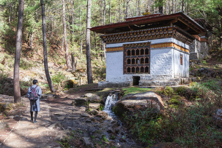 Male tourist in Bhutanese traditional dress walks pass water power prayer wheel on the way to Taktshang monastery (Tigers nest) in Paro,Bhutan