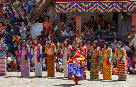 Paro,Bhutan-Apr 4,2015;Buddhist lama performs mask dance in front of group of Bhutanese female singers in beautiful traditional costume at Rinpung Dzong during Paro Tshechu
