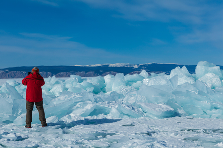 Male tourist in red jacket is taking a beautiful landscape in a nice clear blue sky day in front of the ice hummocks at Olkhon island in frozen Baikal lake,Siberia,Russia