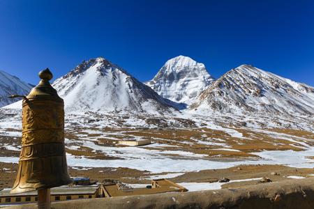 前景に金色のチベットの傘で雪に覆われた神聖なカイラッシュ山の美しい風景北の顔、背景に澄んだ青空、中国