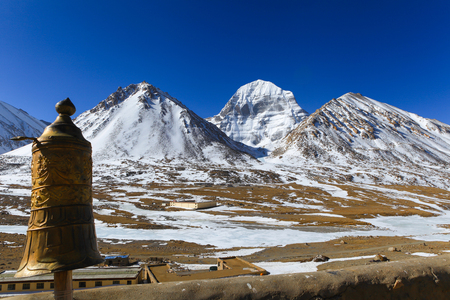 Beautiful scenery North face of sacred Kailash mountain covered with snow with golden tibetan umbrella in foreground and clear blue sky in background,China