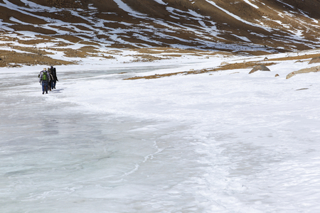 Group of tourist are walking on the frozen river covered with snow on the way to sacred Kailash mountain,Tibet,China
