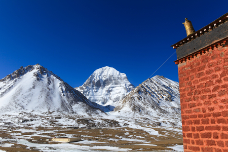 Beautiful scenery North face of sacred Kailash mountain covered with snow with old red brick building with golden tibetan umbrella on top in foreground and clear blue sky in background,China