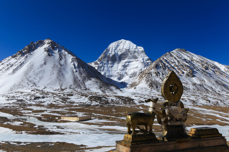Beautiful scenery North face of sacred Kailash mountain covered with snow with gloden deer and dharma wheel in foreground and clear blue sky in background,China