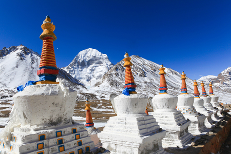 Beautiful scenery North face of sacred Kailash mountain covered with snow with group of white tibetan chortens(pagoda) in foreground and clear blue sky in background,China Zdjęcie Seryjne