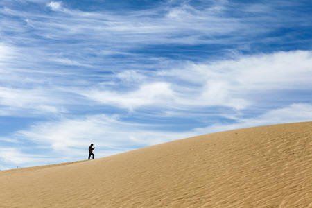 A lonely man walks up the beautiful sand dune showing amazing texture surface and interesting lines of white clouds on blue sky in background,Tibet,China