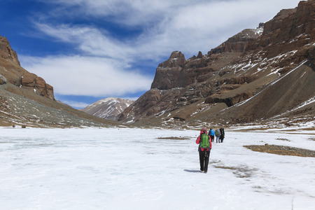Group of tourist are walking on the frozen river covered with snow with high and huge mountain in background on the way to sacred Kailash mountain,Tibet,China