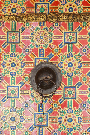 Brass tibetan doorknob on the door painted with colorful lotus flower design