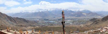 Panoramic view of Lhasa cityscape with snow capped mountain range in background and a flag pole in the middle from Drepung monastery,Tibet,China