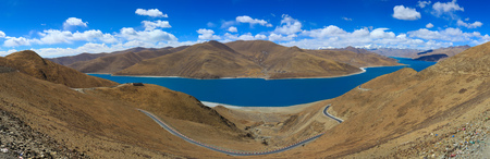 Panoramic view of beautiful turquoise holy Yamdrok lake with curved road and himalaya range,blue sky with white clouds in background,Tibet,China Zdjęcie Seryjne