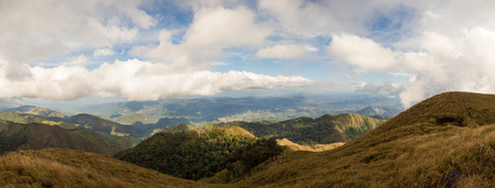 Panoramic view of mountain range coverd with brown grass field and green tropical rain forest with cloudy sky in the western part of Thailand