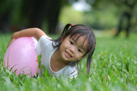Asian little girl with pink balloon and lies on green grass