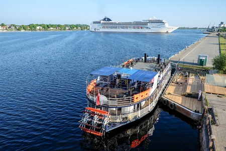 perle: Ocean Cruise Ship MSC Opera turning round on Daugava river and Touristic river boat Pearl of Riga - Rigas perle - with paddle wheel by the Riga city embankement, Latvia