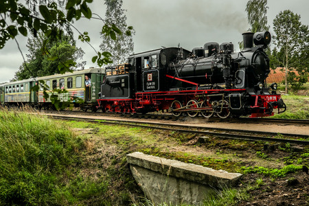 narrowgauge: Aluksne, Latvia - August 6, 2016: Real narrow-gauge railway steam locomotive driving over a small bridge with passengers aboard