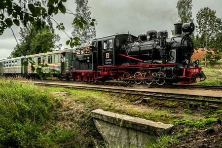 footplate: Aluksne, Latvia - August 6, 2016: Real narrow-gauge railway steam locomotive driving over a small bridge with passengers aboard