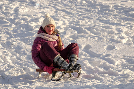 sledging people: Active young cute girl sledding down the hill on sunny winter day