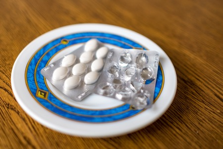 Set of pills in a plastic and foil package lying on white tray with blue rim