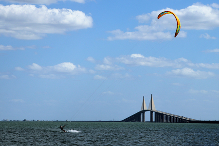 Kite surfer gaining air with a kite above as he attempts to jump the skyway bridge