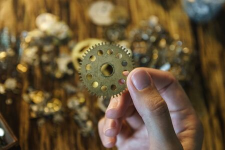 Watch repairer holds large gear. Big metal gearwheel on blurred workspace. Cogwheel on blurred background of workplace. Pinion in female hand. Old cogwheel on wooden table background.