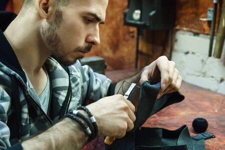 Craftsman intently works with leather. Tanner sews leather goods. Making handmade stuff. Male hands with needle and thread. Man working with needle and pliers.