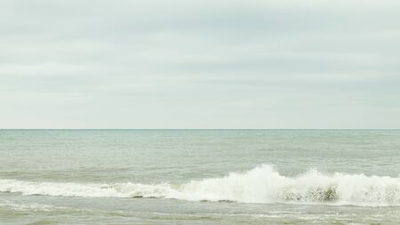 Bursts of seawater. Waves near seashore. Dark cloudy sky over sea. Water spray on shoreline. Gray heaven over the bay.