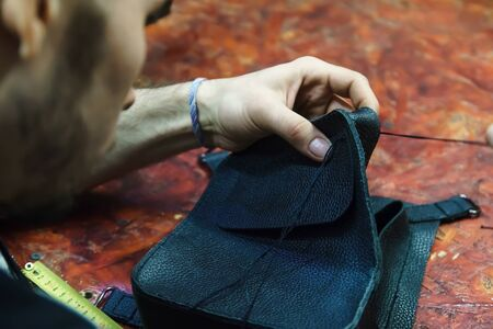 Craftsman intently works with leather. Tanner sews leather goods. Making handmade stuff. Male hands with needle and thread. Man working with needle. Stockfoto