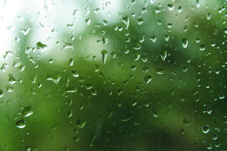 Beautiful view from window at dim outlines nature backdrop. Water drops on glass with blurred edges. View from window on rainy day. Rain drop on windowpane with blur tree background.