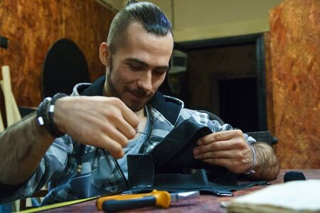 Tanner sews leather goods. Craftsman smiles while working. Making handmade bag. Male hands with needle and thread. Skinner working with needle and pliers.