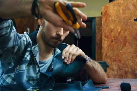 Young man sews leather goods. Craftsman creates leather object. Making handmade item. Guy working with needle pliers. Male hands with needle and thread