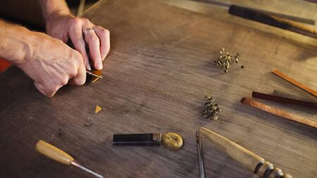 Tanner cuts out leather goods by cutter. Craftsman works by knife in workshop. Stock fotó