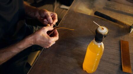 Tanner glues details. Small business concept. Male hands close up holding working with leather in workshop.