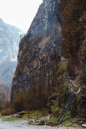 Stone bag Abkhazia in spring. Canyon road surrounded by rocks. Trees grow on ridge. Cliffy mountains above way. Unusual place in mountainous areas. Ladder goes up hill. Steep stairs near road.