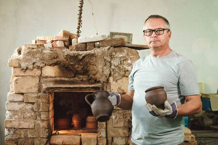 Master potter stands near pottery kiln and show his product. Imagens