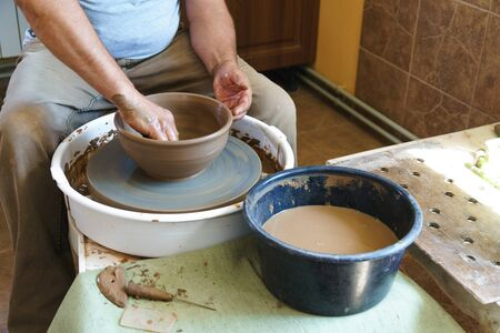 Master potter works with clay in pottery workshop.