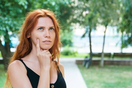 Pensive girl thinking about something in park. Young redhead woman looks away. Problem of choice.