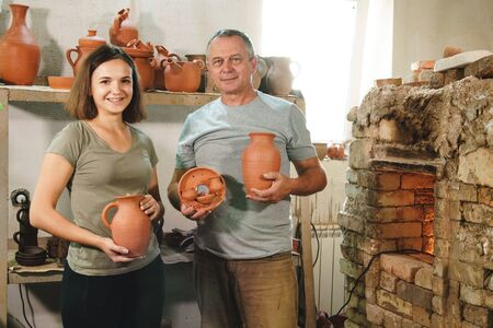 Father and daughter potters on brick pottery kiln background. Artisans holding products in hands. Family business concept.