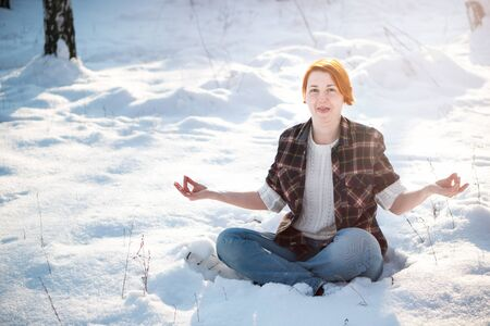 Young woman meditating alone winter forest. Joyful and happiness concept. Stock Photo
