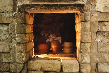 Clay pot and jug in brick pottery kiln. Element of authentic workshop.