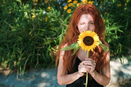 Redhead girl squint in sunlight. Young woman with tousled red hair in garden, copyspace. Standard-Bild