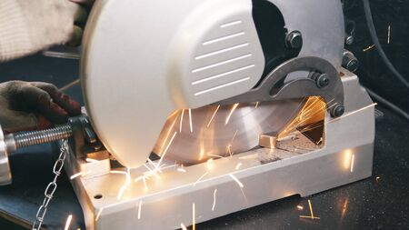 Working man with big saw cutting metal. Grinding in steel manufactory. Iron work concept.