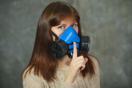 Young woman in respirator shows sign of silence on grey background. Virus protection concept.