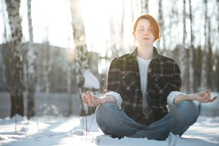 Young woman with nordic appearance sitting in yoga position in frozen forest. Girl meditating and contemplating scenery. Winter day on holiday, outdoor. Freedom concept with copy space.