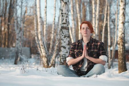 Girl in winter forest in lotus pose. Adherent of doctrine of yoga in frosty weather. Tranquility and concentration concept with copy space. Фото со стока